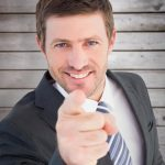 composite-image-of-businessman-smiling-and-pointing
